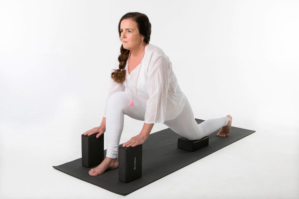 pessoa faz postura de yoga numa aula particular